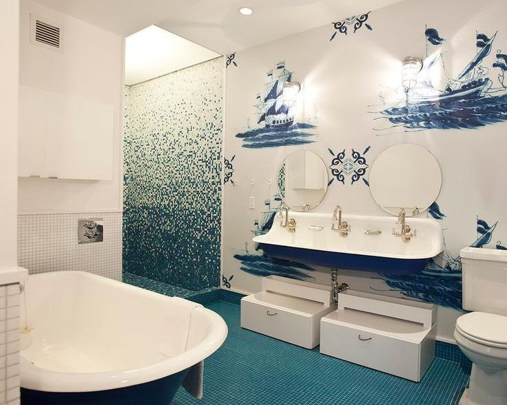 Blue nautical boys' bathroom features an accent wall painted with blue ships lined with white steps tools adorned with rope hardware tucked under a blue trough sink fitted with three faucets by Kohler as well as round frameless mirrors.