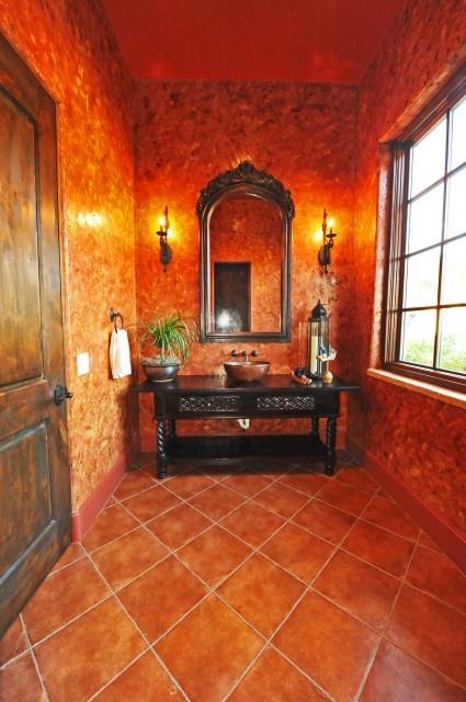 would make a lovely washroom. orange walls, orange tiled floor, black wooden washstand with copper bowl, large mirror