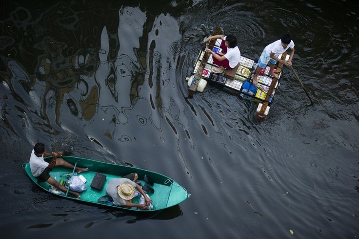 Thais use improvised rafts to float around in flooded Bangkok - Photos