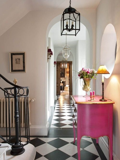 Love the black and white floors with the pink chest, rounded doorways and windows, elegant stairway