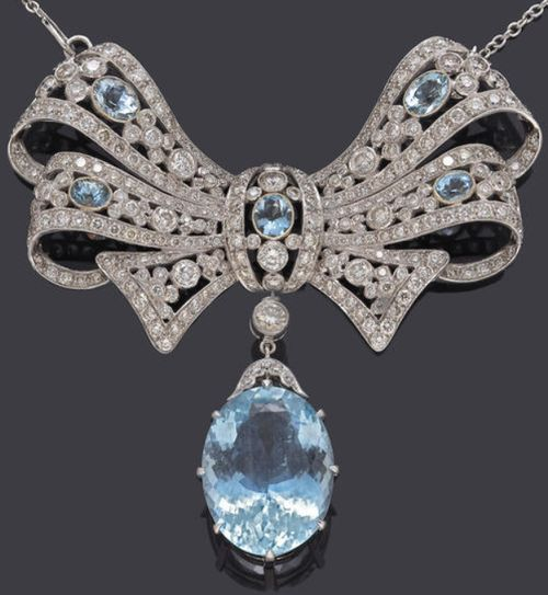 An aquamarine and diamond brooch-pendant-necklace with removable drop and chain aquamarine weighing 21.78 carats; remaining aquamarines weighing approximately: 2.60 carats; estimated total diamond weight: 9.00 carats; mounted in eighteen karat white gold; length: 17 1/4in. Via Bonhams.