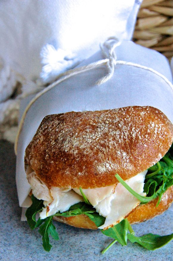 Perfect picnic sandwich: Roasted chicken sandwich with avocado, arugula, sharp white cheddar, dijon mustard, and parmesan ranch dressing on crusty bread.