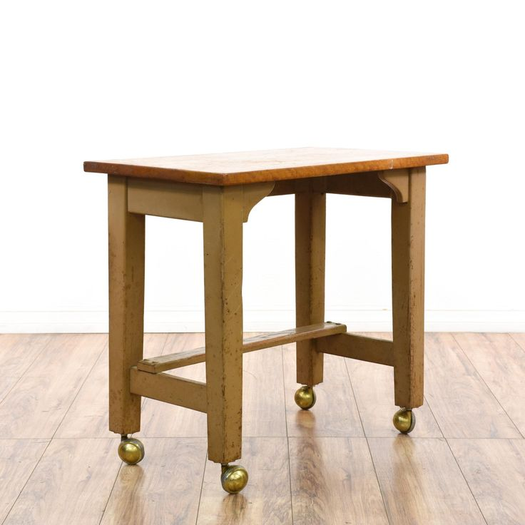 This rustic industrial console table is featured in a solid wood with a distressed oak and beige paint finish. This kitchen cart table has rolling brass caster wheels and a stretcher base great for adding a bottom shelf. Perfect as a small kitchen table for additional table top space! #americantraditional #tables #consoletable #sandiegovintage #vintagefurniture