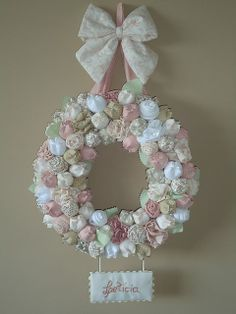 Flores de tecido na guirlanda de enfeite da maternidade, com o nome do bebê
