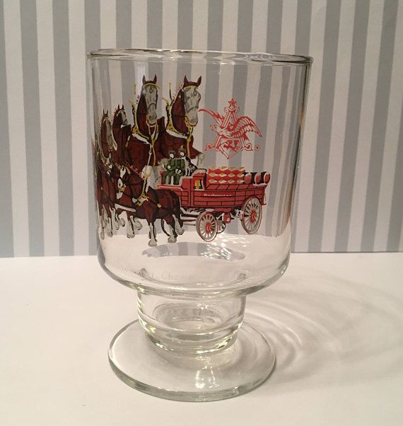 The Budweiser Clydesdales made their first-ever appearance on April 7, 1933. A gift from August A. Busch, Jr. and Adolphus Busch to their father in celebration of the repeal of Prohibition. While I cant send this team of famous horses to your house, I can ship you this glass if you like it!  This item is a Budweiser Champion Clydesdales glass (ca. 1980s), depicting the famous team of Budweiser horses pulling the Budweiser wagon on its way to make some thirsty person very happy!  The glass is…