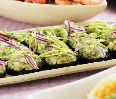 Klassisk gubbröra med ansjovis, hårdkokta ägg, kaviar, rödlök, äggula och finhackad gräslök. Bred gubbröran på skivor av pumpernickel och garnera med tunna skivor rödlök.