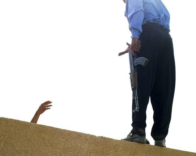 Irak, Najaf 20.09.2003 r. Iracki policjant strofuje Irakijczyka zbyt blisko podchodzącego do posterunku