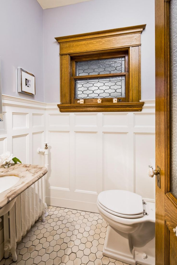 As seen on Rehab Addict, Nicole Curtis restored the powder room off the grand staircase to period appropriate style after it had been completely gutted. The wainscoting  from the hallway and has been replicated and given four coats of lacquer for a classic feel. 1970s fixtures on the sink were replaced, and the gold painted basin was stripped back to the original porcelain.