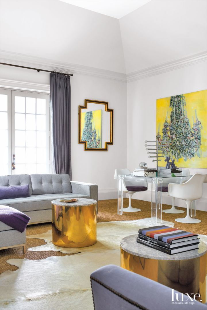 """In the living room, sculptures by Joseph Havel are ethereal in presentation. """"They're old book pages buried in Lucite,"""" says interior designer Elisabeth McCabe. Additionally, the designer juxtaposed a pair of white barrel chairs with vintage crystal sconces and a fanciful Hal Bienenfeld Art Deco mirror."""