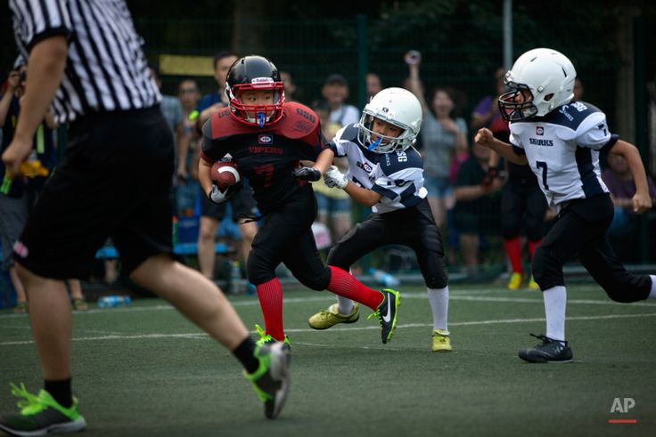 In this Sunday, July 5, 2015 photo, a young player dodges a pair of opposing tacklers during their American football game in Beijing. (AP Photo/Mark Schiefelbein)
