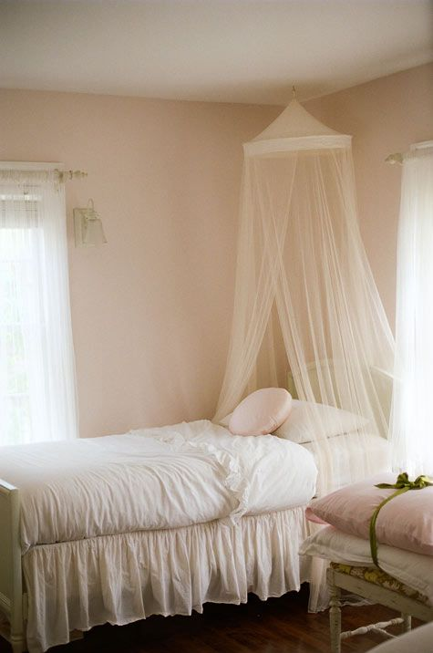 Love the ribbons around the pillows (or linens) and the netting over the bed.