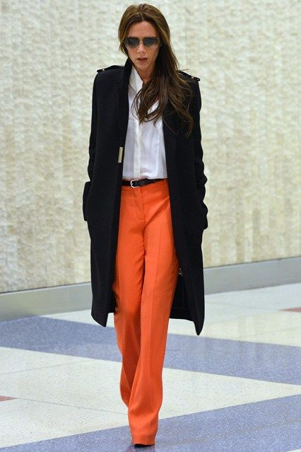 Victoria Beckham arrived at JFK airport wearing orange wide-leg trousers  with a white shirt