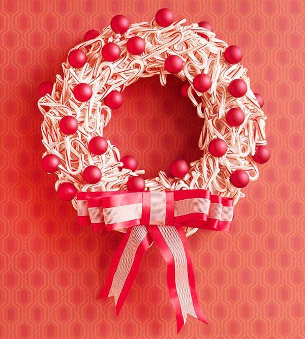 Ghirlanda natalizia fai da te con bastoncini di zucchero e palline rosse