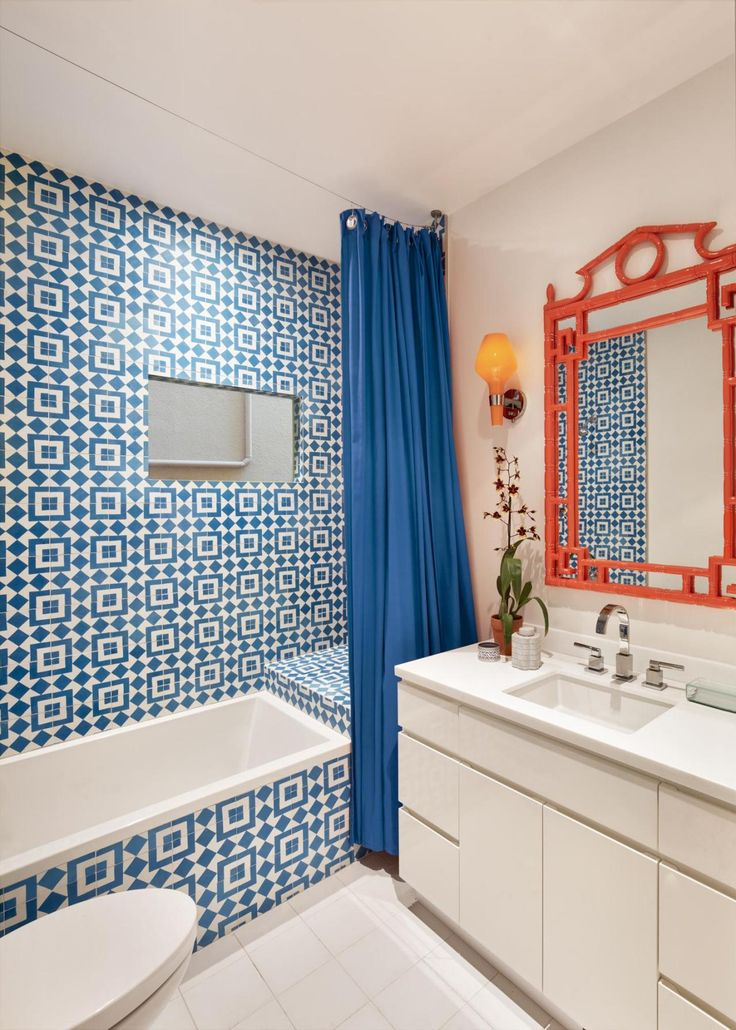 modern kids bathroom with blue orange accent This fun kids bathroom is bursting with color and pattern. Eye-popping hues of complementary blue and orange set the tone for a fun, creative space kids are sure to love. Meanwhile, clean white walls, floors and cabinets allow the colorful accents to steal the show.