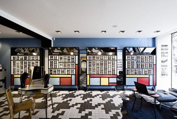foorni.pl   Naocznie niestandardowy – nowoczesny salon optyczny, regały z czerwonymi, żółtymi i niebieskimi szafkami z czarnymi konturami wokół drzwiczek
