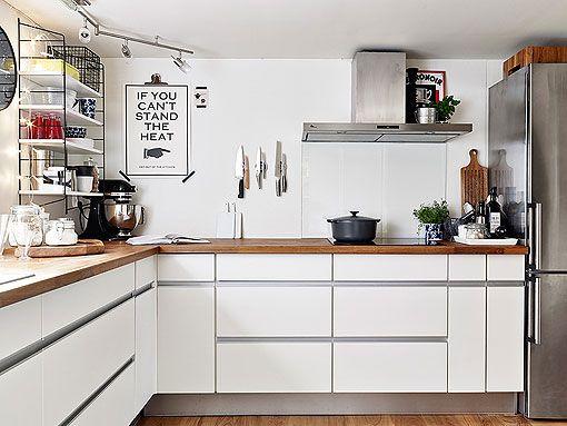 cocina con muebles blancos encimera de madera y de acero