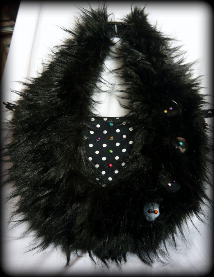 Fekete szőrmés-pöttyös táska -Handmade by Judy Majoros:Fekete textilbőrből készült ez a bohém táska A textilbőr fekete-fehér pöttyös viszkóz anyagú borítást kapott, erre pedig hosszú szőrű műszőrme került. A műszőrmét nagy gombok és színes gyöngyök díszítik. A fehér pöttyök színes gyöngyökkel lettek feldobva. Kézitáskaként és keresztben is hordható, ugyanis vállpántja műanyag táskacsattal van rögzítve a táskához, így lecsatolható. Hátulján egy pöttyös zseb található ami tépőzárral záródik.