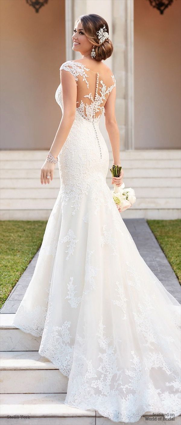 This tulle over organza fit and flare Stella York wedding dress features light-catching clear beading on embroidered lace throughout. The dramatic illusion back zips up with ease under gorgeous fabric-covered buttons.