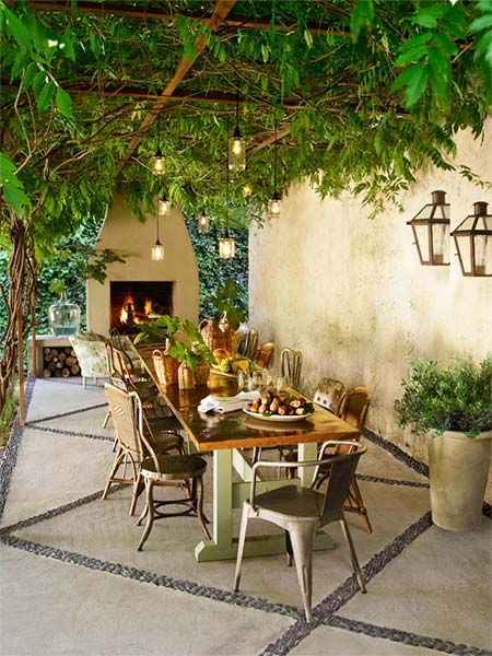 outdoor tuscan-style dining area with copper topped table, wood-burning oven, a mix of wicker chairs, and rustic hanging and wall-sconce lighting