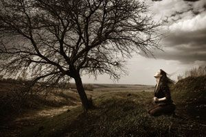 woman sitting under a bare tree
