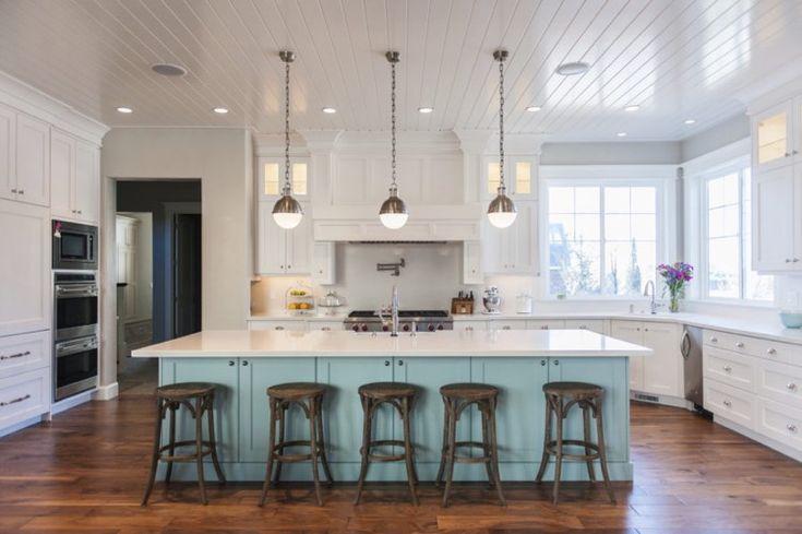 grande cuisine lumineuse aménagée avec des armoires blanches et un îlot central avec rangements bleus