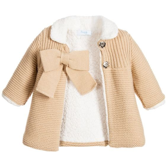 Baby girls beige pram coat by Foque with a large bow on the front. Made in knitted acrylic, the bodice has a linear pattern and does up with large concealed poppers. The collar is in cosy synthetic sheerling with an ivory needlepoint lining. Warm synthetic sheerling also lines the coat and forms the cuffs. A beautiful pram coat for little girls to wear when out and about or as an extra cosy cardigan.