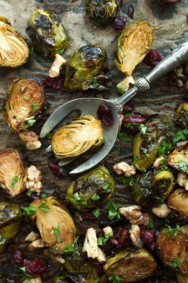Karmelizowana brukselka z żurawiną  Przygotowanie:      500 g brukselki      2 łyżki oleju roślinnego      1 łyżka octu balsamicznego     2 łyżeczki syropu klonowego     1/4 łyżeczki papryki wędzonej     1/4 łyżeczki papryki ostrej      sól i czarny pieprz      2 łyżki posiekanych, podprażonych orzechów włoskich     2 łyżki suszonej żurawiny     2 łyżki posiekanej pietruszki, bardzo drobno     sól i czarny pieprz     opcjonalnie do polania: kilka kropel syro