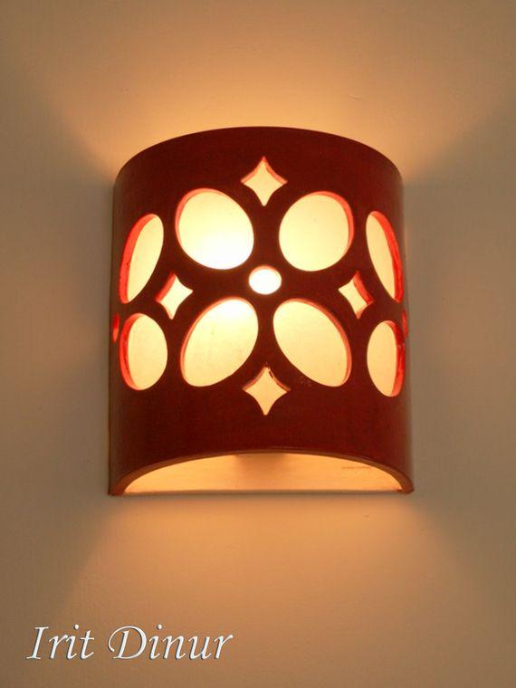 """גוף תאורה צמוד קיר מקרמיקה בצבע אדום.  מידות 22*18 ס""""מ. מנורת קיר מקרמיקה בעבודת יד, בגוון אדום. במידות רוחב 18 ס''מ, גובה 22 ס''מ, עומק 8 ס''מ. האור מתפזר כלפי מעלה ומטה וכן דרך העלים שבדוגמה. ניתן להזמין בצבעים ובכמויות שונות. (הזמנות מיוחדות יחויבו במחיר המלא של המוצר)."""