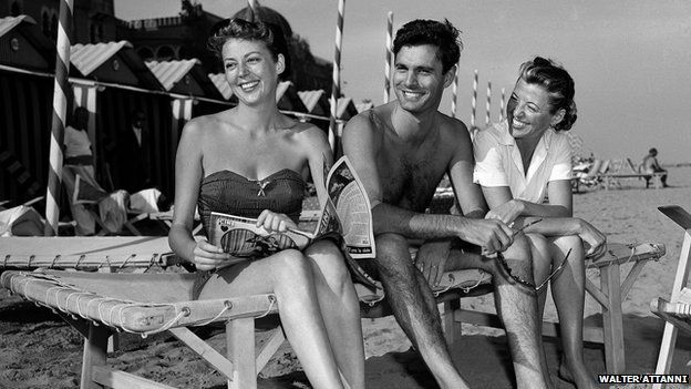 Louis Jourdan sits with actress Anne Vernon, left, and his wife Berthe Frederique in Venice, Italy, in 1952