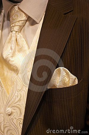 Part of a beautiful brown wedding tuxedo for men with cream colored necktie and vest as a closeup image