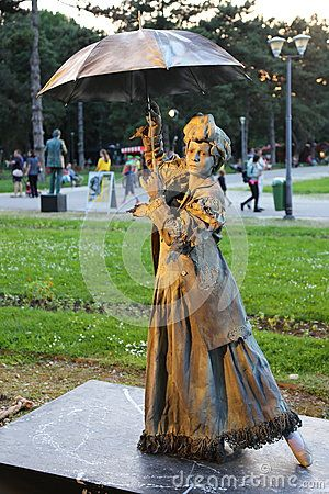 Living statue - lady with umbrella at international festival of living statues in Bucharest, Romania.