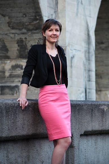 Olivia en veste de tailleur courte, jupe crayon rose et sautoir H&M