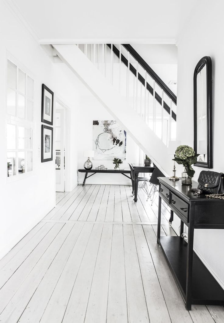 Keeping black as an accent helps keep this monochrome corridor feeling light and breezy.