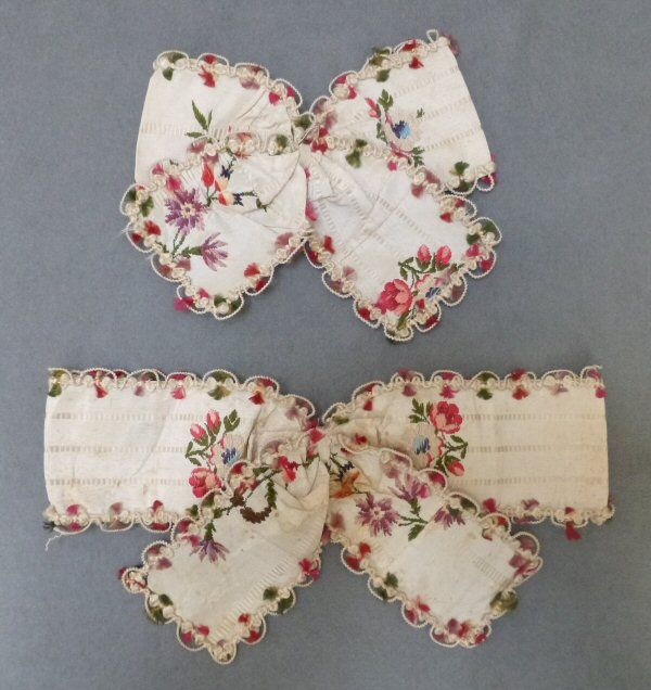 Bows, robe à la francaise, England (Spitalfield's), 1760s, remodeled 1780s. Ivory ground silk taffeta woven with a narrow self weave stripe, with gently curving flower and leaf meanders in puce, shaded tangerine flowerheads, red berries and sage green foliage, alternating with small sprays of flowers in deep rose pink and ivory. Trimmed with same tufted silks and corded wire loops. Bows worn on sleeve ruffles.