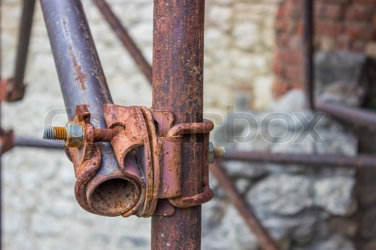 Stock image of 'Detail of vintage and rusty scaffolding clamp with pipes'