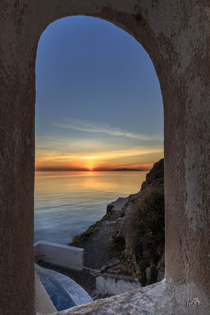 A spectacular sunset view, through the arc on St Nicolas islet in Oia village, Santorini island, Greece - Selected by www.oiamansion.com