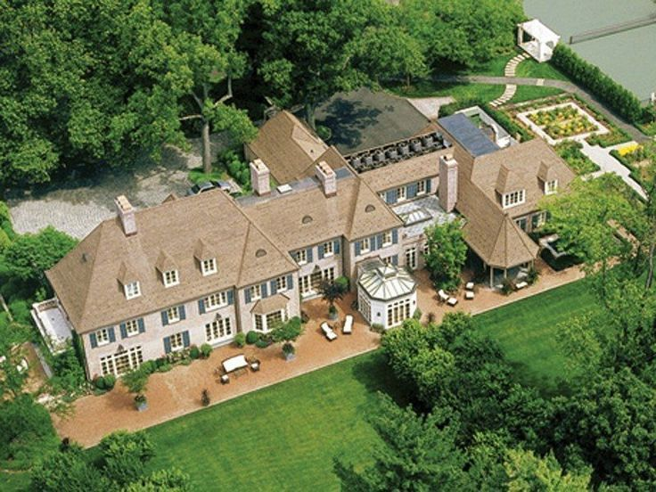 This renovated English Manor in the Connecticut countryside has white washed brick walls, blue shutters, colonial style windows, dormer windows, balconies, stone terraces, structured gardens and manicured landscaping.
