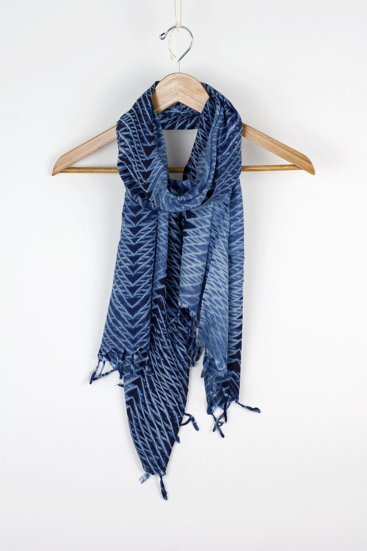 This 100% silk scarf is hand crafted using only natural dyes in the arashi shibori technique, featuring stunning multi-directional lines in cascading layers. Perfect for any denim day. Available in In