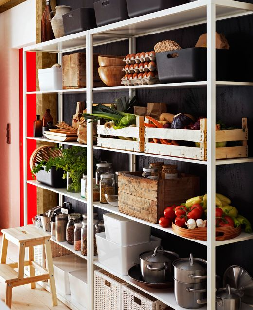 Two IKEA shelving units filled with pots, jars and baskets and boxes holding produce.