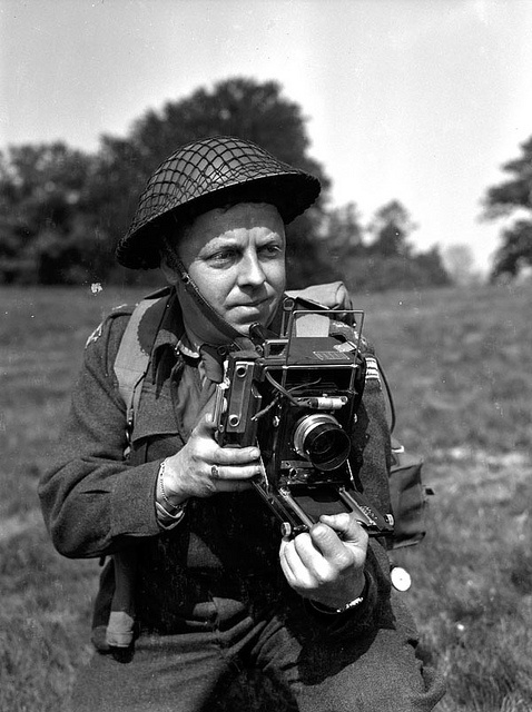 Lieutenant Frank L. Dubervill of the Canadian Army Film and Photo Unit, holding an Anniversary Speed Graphic camera in England (May 11, 1944)