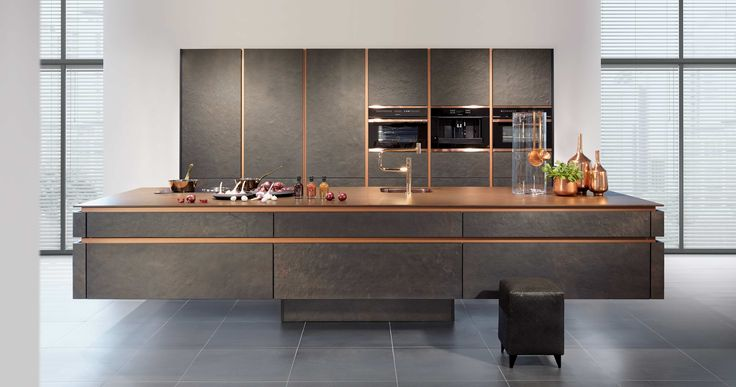 A real stone kitchen as an intentional and provocative contradiction to floating bodies. The dialogue between rough, dark slate structure and shiny, light copper. A relationship of tension, that eventually leads to a perfect harmony of colours.