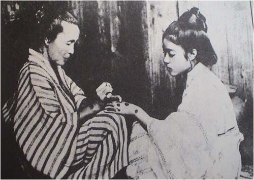 1919- a young Okinawan woman is tattooed with hajichi, a practice outlawed in 1899.