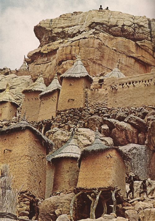 """Propped by rubble, logs, and faith, a family compound at Yenndouma, Mali, clings to a rock face."" (National Geographic, 1969)"