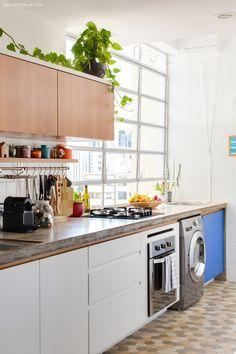 Área de serviço integrada à cozinha tem bancada de concreto e marcenaria que varia entre o tom natural da madeira, azul e branco.