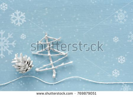 Christmas and New Year background. White Christmas tree made from dry twigs cone decoration on light blue backdrop with snowflakes