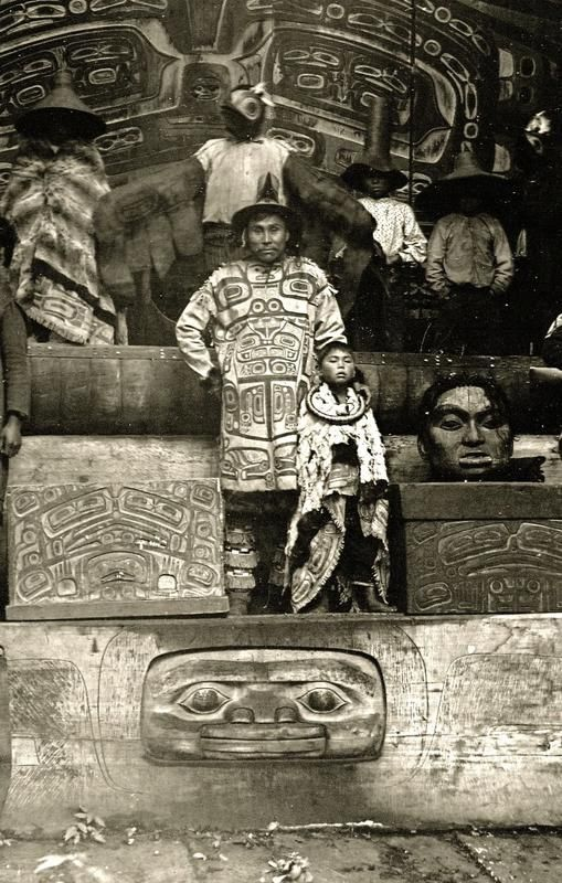 The Whale house family of Gaanaxteidi men among their at.oow (sacred items). <br><br>   In the centre stands Kuwdu.aat, with his son. Kuwdu.aat and his boy stand between two decorated bentwood boxes that hold the lineage's sacred items. On top of the one on their right is a mask made in the image of X'akat. ahan, the woman who raised the Wood Worm.<br><br>     (description given by Jennie Thlunault in Nora Dauenhauer and Richard Dauenhauer. Has K̲usteeyí, Our Culture:...