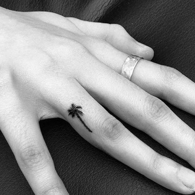 With a tiny palm tree inked on your finger, you'll never feel too far from the beach. RELATED: 17 Celebrity Tattoos and Exactly What They Mean