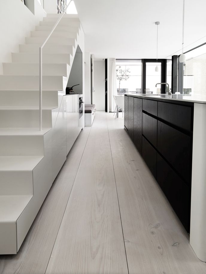 Wide lime washed floorboards, black kitchen units, white stairs.