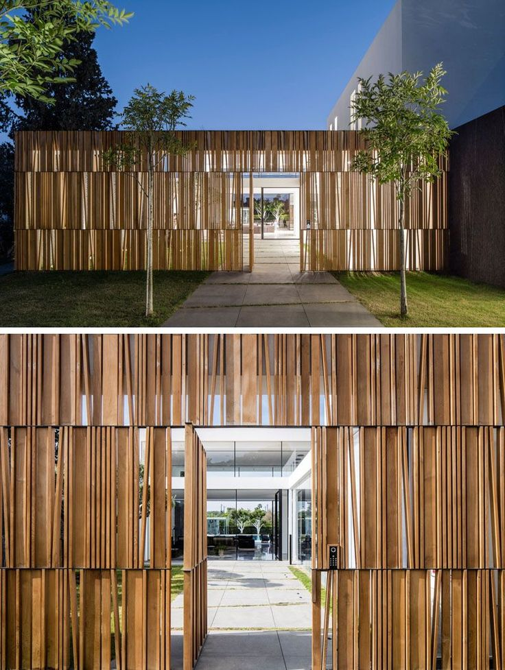 To enter this home, you walk down a tree lined path and through a wooden facade that partially blocks the view to the inside of the home.