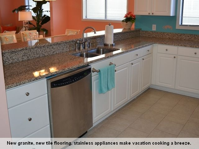 New beach kitchen decor - new white cabinets, new tile flooring, new stainless steel appliances, and granite countertops. http://www.rudd.com/rentals/properties/southern-shore-villa-113/